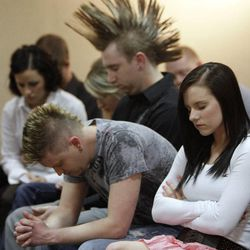 """Family and friends of Matthew David Stewart bow their heads during a prayer during a """"Keep the Peace"""" rally in Ogden Thursday, April 12, 2012. Stewart, a decorated former U.S. Army soldier, is charged with capital murder in the shooting death of Ogden police officer Jared Francom."""