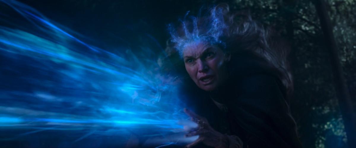 La madre de Agatha Harkness lanza magia azul de sus manos mientras le da una corona mágica azul en WandaVision.