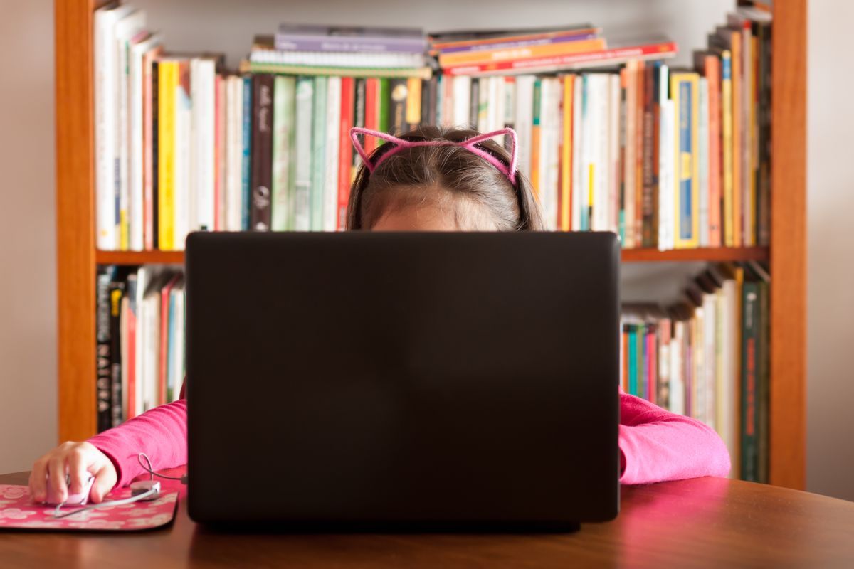 A young girl with a pink cat ear headband works on a laptop.