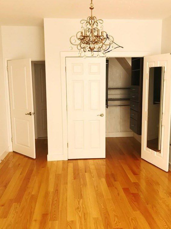An empty bedroom with an empty open closet.