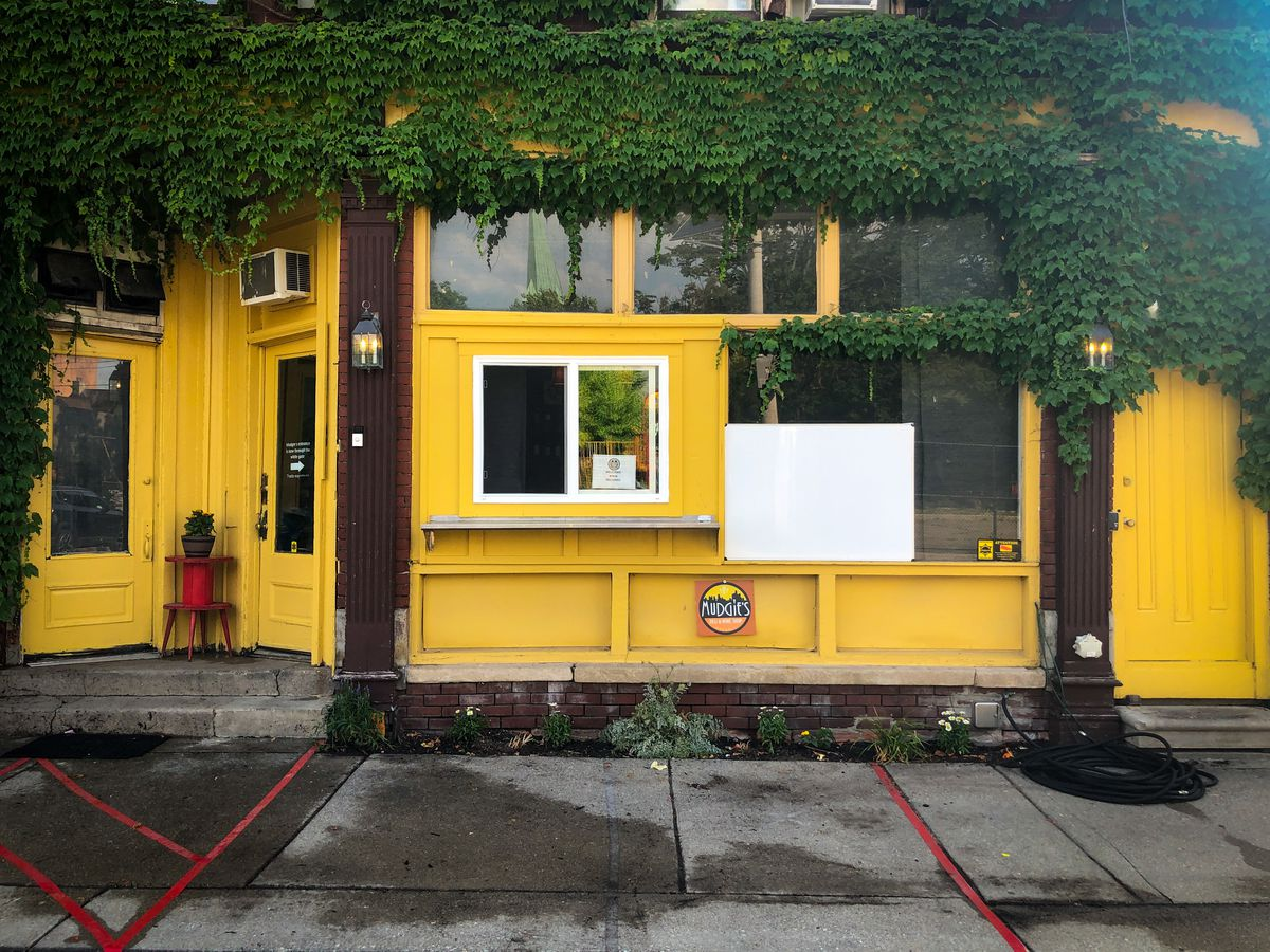 Ivy and yellow painted walls surround a walk-up window at Mudgie's Deli in Corktown.
