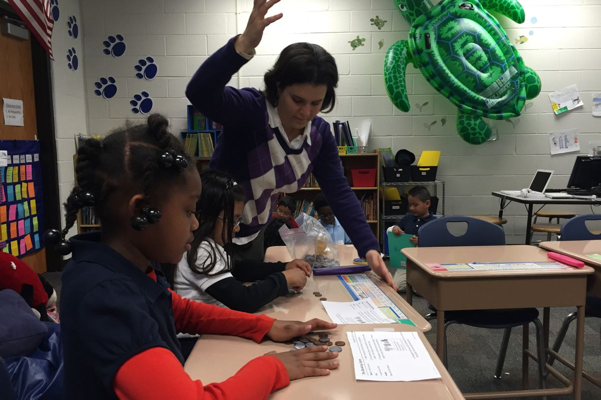 Shana Nissenbaum, a third-grade teacher at the now-closed Key Learning Community School, helps a group of students with a math activity on counting money.