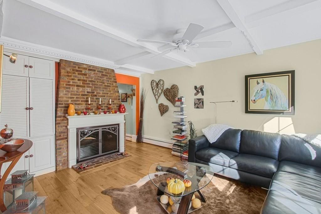 The same living room, but now with the brick fireplace feature prominently.