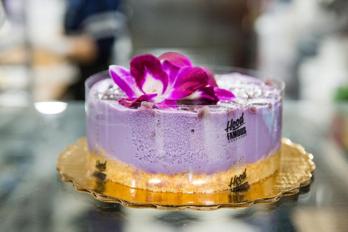 A purple ube cheesecake with a colorful flower on top.