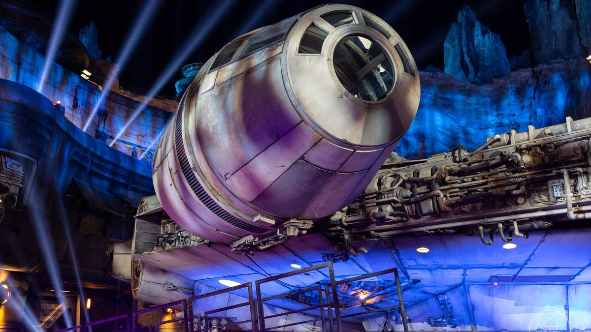 Galaxy's Edge in Disneyland, the evening of a special press preview before opening day. Lights play across the hull of the Millennium Falcon, while massive spotlights arc through the sky.