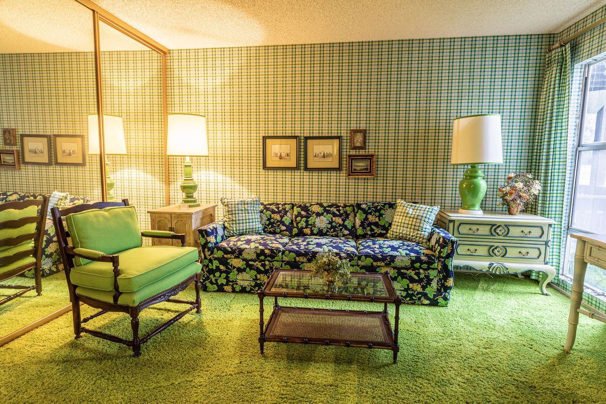 A room with solid green carpet and patterned green wallpaper. A solid green armchair sits next to a green and dark blue patterned sofa.