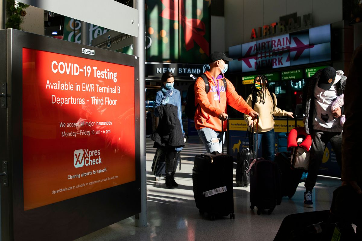 Travelers with rolling luggage walk through an airport past a sign about Covid-19 testing.