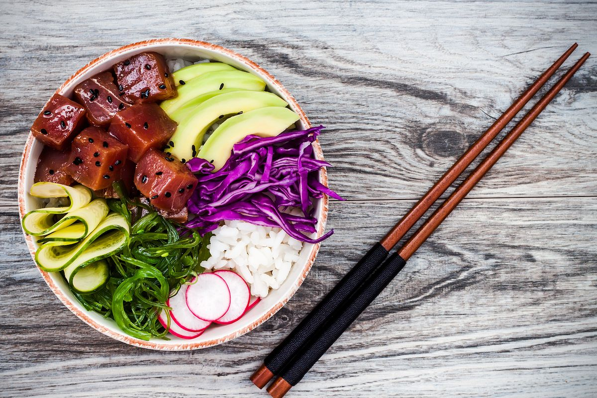 A poke bowl with seaweed, avocado, red cabbage, radishes and black sesame seeds.