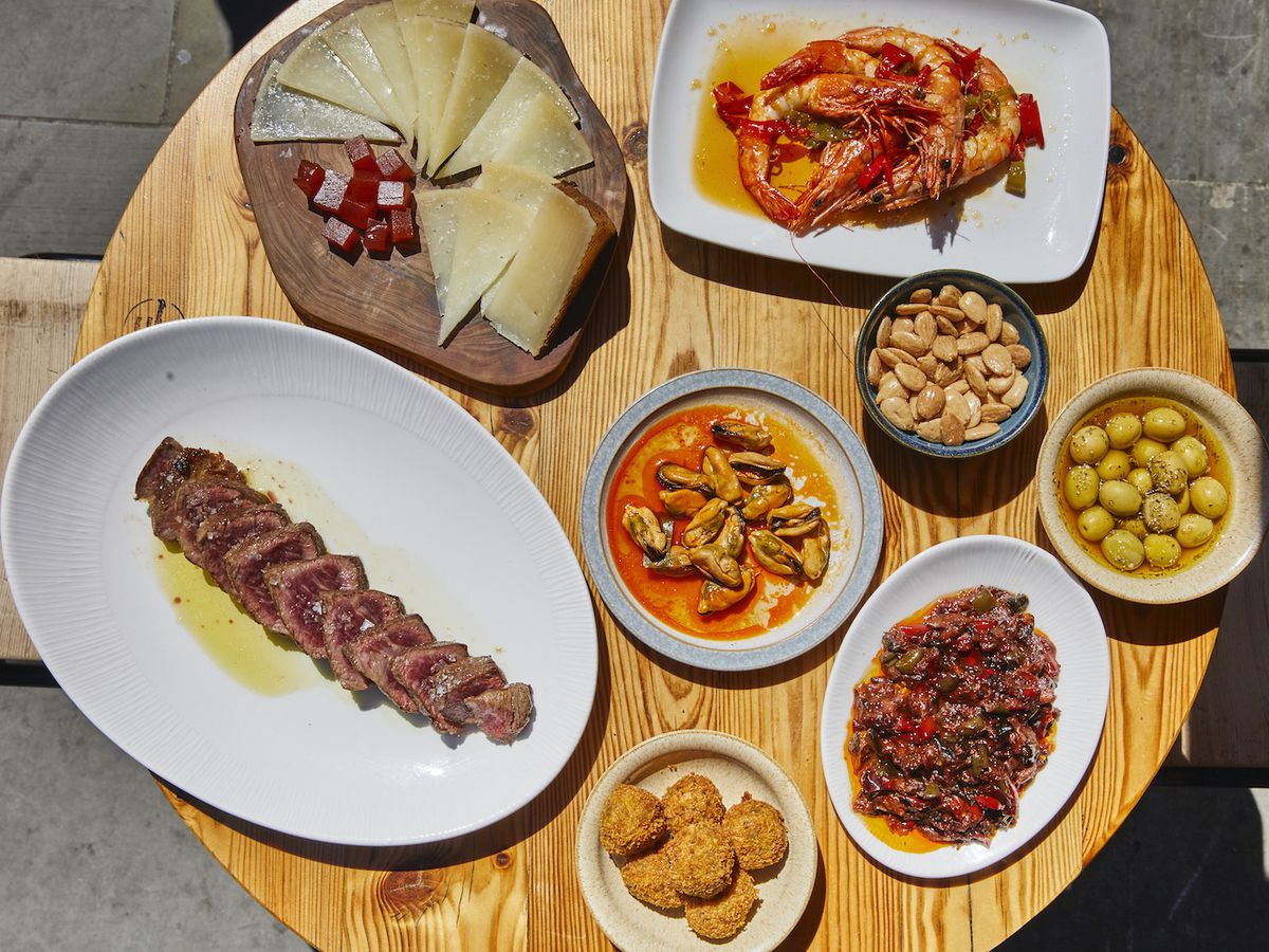 A table of José Pizarro's Spanish classics, including Ibérico presa with flaky salt; red prawns in chilli and garlic; croquetas; olives; cheese; and escalivada