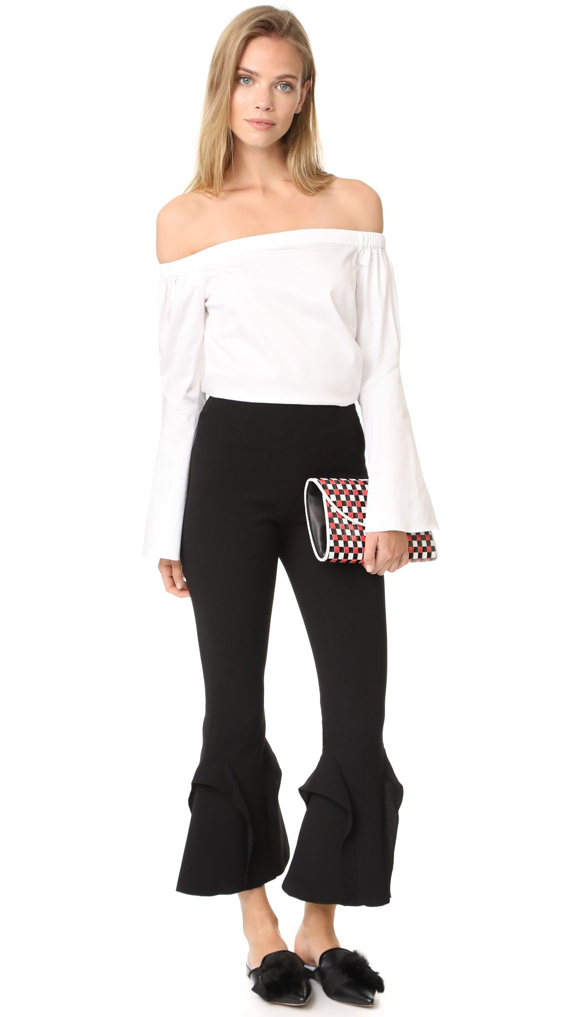 A model in a white top and black frilled pants