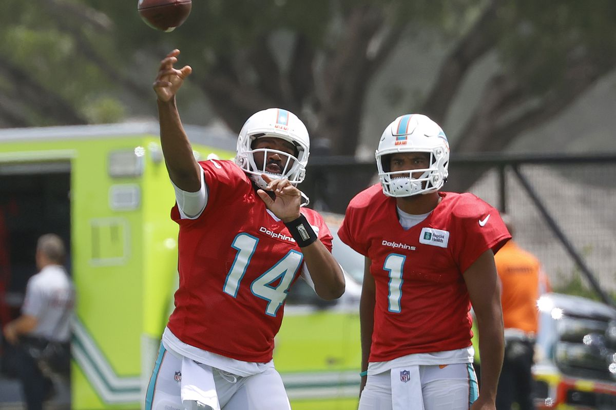 Tua Tagovailoa #1 watches as Jacoby Brissett #14 of the Miami Dolphins throws the ball at the Baptist Health Training Complex on August 25, 2021 in Miami Gardens, Florida.