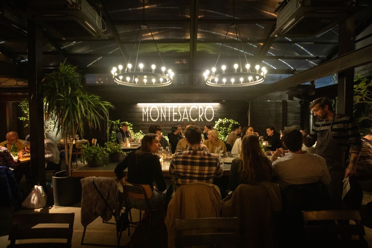 A huge darkened room with potted plants and a lit sign featuring the name of the restaurant, with several tables in front.