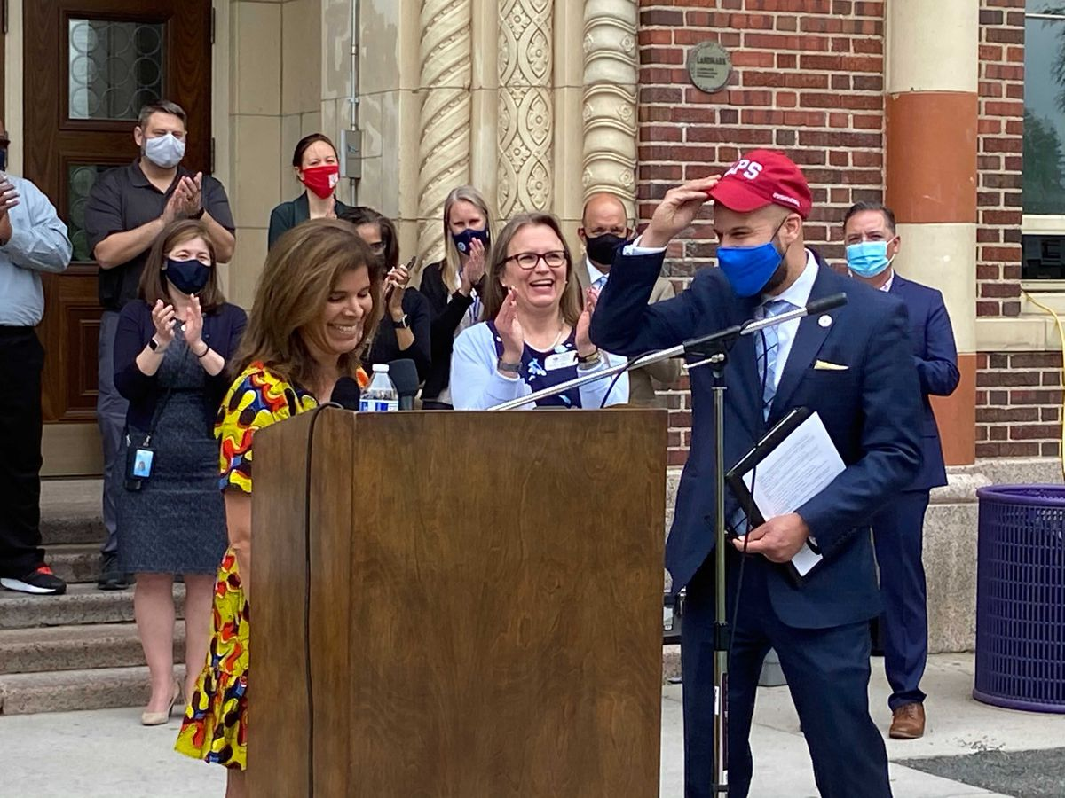 Denver Public Schools Foundation President Veronica Figoli, wearing a yellow, black and red dress, gives a red Denver Public Schools hat to Dr. Alex Marrero, wearing a blue suit, white shirt, blue tie and blue mask. They are standing at a podium while onlookers applaud.