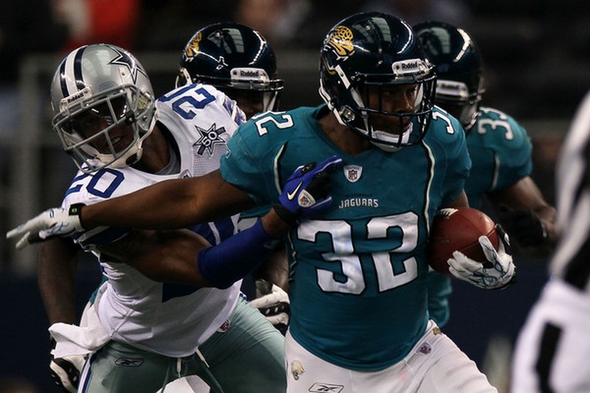 ARLINGTON TX - OCTOBER 31:  Maurice Jones-Drew #32 of the Jacksonville Jaguars runs the ball against Alan Ball#20 of the Dallas Cowboys at Cowboys Stadium on October 31 2010 in Arlington Texas.  (Photo by Stephen Dunn/Getty Images)