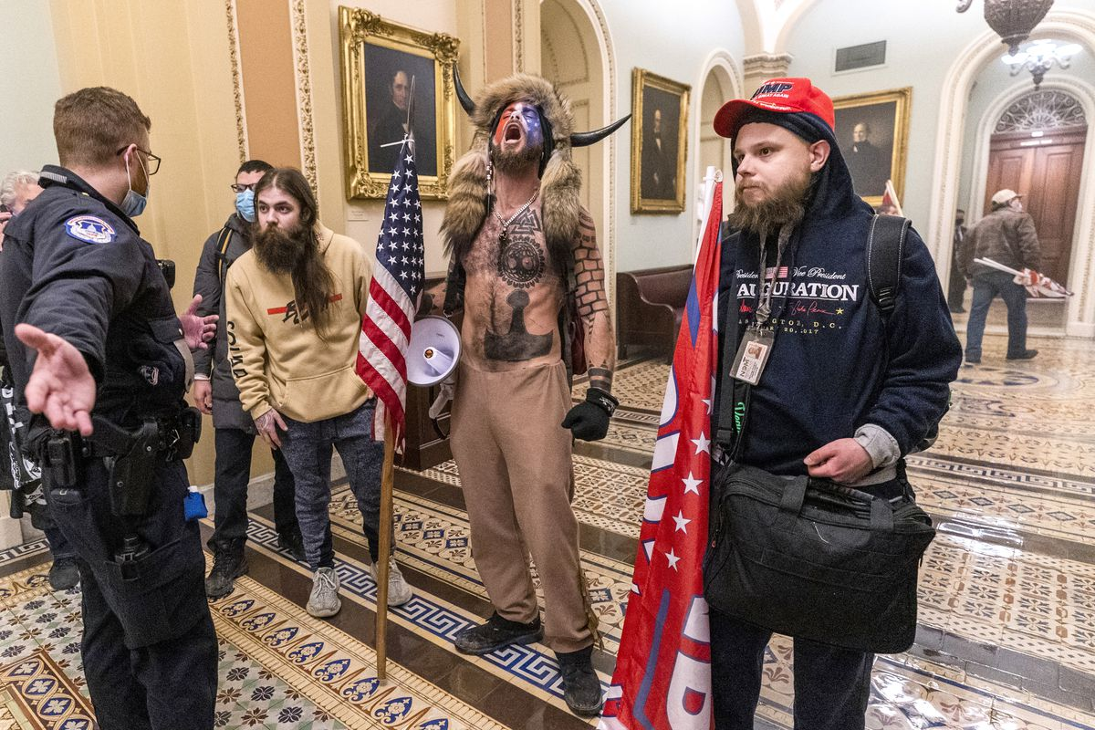 Supporters of President Donald Trump, including Jacob Chansley, center with fur hat, are confronted by Capitol Police officers outside the Senate Chamber inside the Capitol in Washington on Jan. 6, 2021.