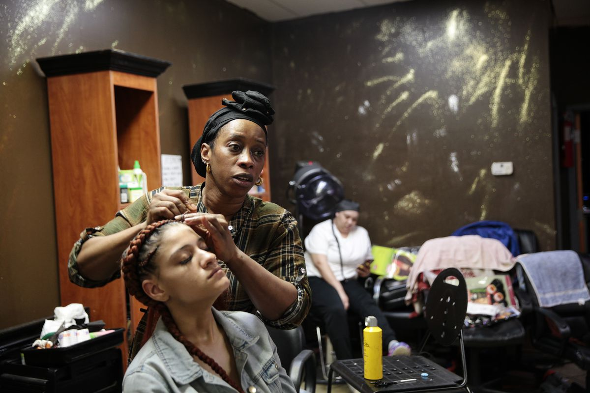 Matilda Kromah, center, braids a clients hair at her salon, Thursday, April 22, 2021, in Brooklyn Center, Minn. The salon was looted after a white police officer fatally shot a Black man this month, and Kromah faced a resurgence of the trauma from the civil war in Liberia she fled over 20 years ago.