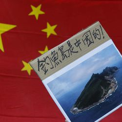 """A protester demonstrating against Japan's claim to disputed islands holds a picture of the rocky islands, known as Senkaku to Japanese and Diaoyu to Chinese, reading """"Diaoyu  belongs to China"""" in front of a Chinese national flag during a rally outside the Japanese Consulate General in Hong Kong, Tuesday, Sept. 11, 2012. A territorial flare-up between China and Japan intensified Tuesday as Beijing sent patrol ships near the disputed East China Sea islands in a show of anger over Tokyo's purchase of the largely barren outcroppings from their private owners."""