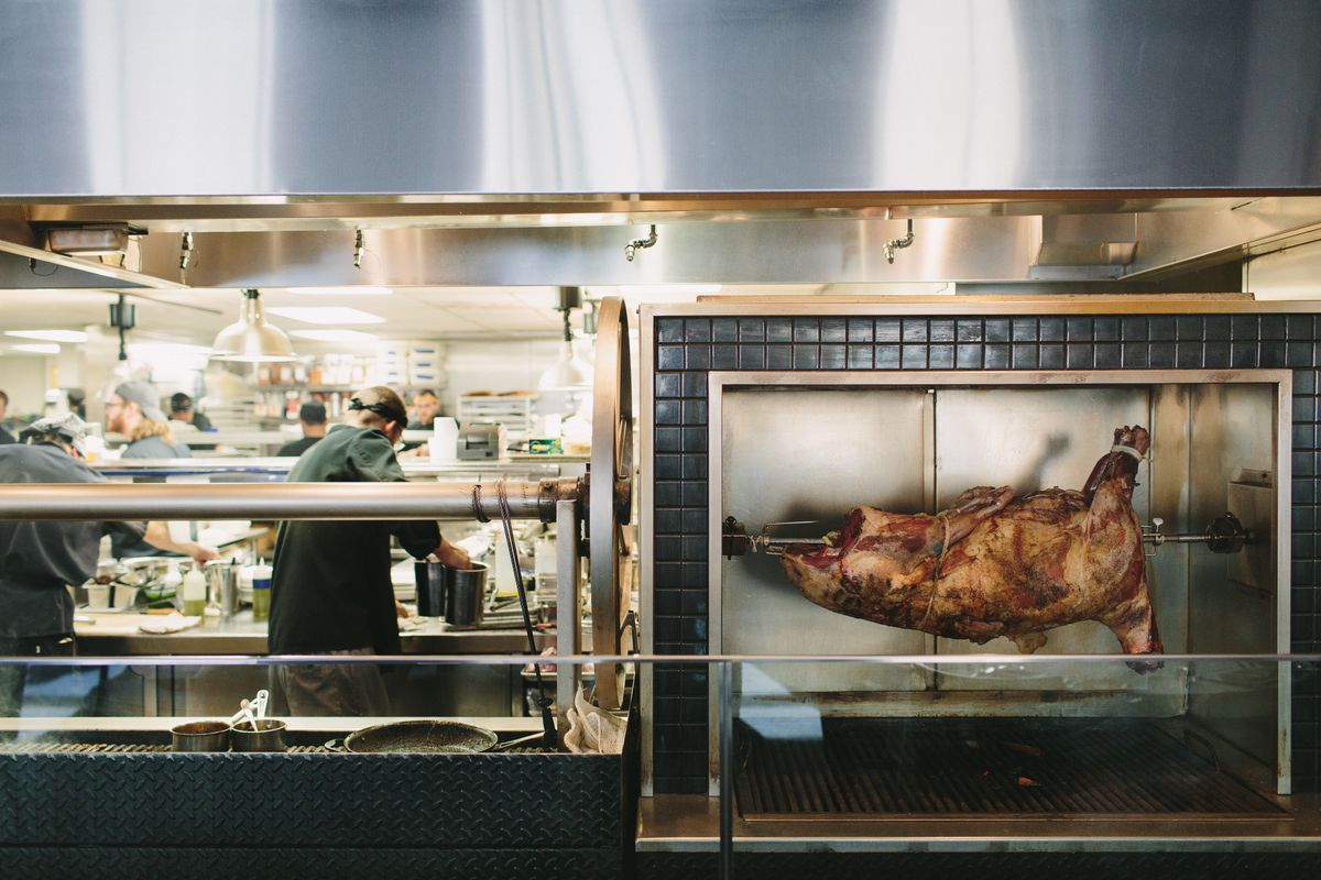 A pig roasting on a spit surrounded by black tile in front of an open kitchen at Roast in Detroit.