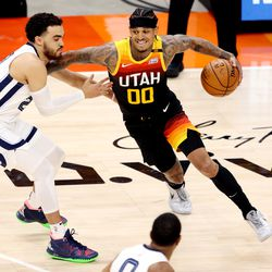 Memphis Grizzlies guard Tyus Jones (21) works to stay with Utah Jazz guard Jordan Clarkson (00) as the Utah Jazz and the Memphis Grizzlies play in game 5 at Vivint Arena in Salt Lake City on Wednesday, June 2, 2021. Utah won 126-110, Utah advances to the second round.