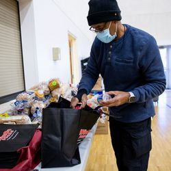 Jack Hesleph, director of evangelism and community outreach at Calvary Baptist Church in Salt Lake City, loads food into bags to be distributed to the homeless on Saturday, Dec. 19, 2020.