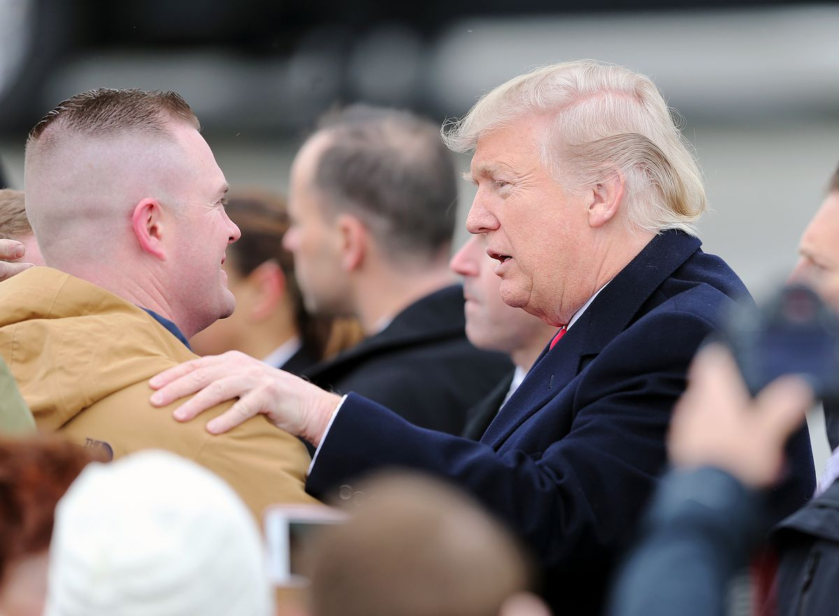 President Donald Trump talks with a man in the crowd as he arrives at Roland R. Wright Air National Guard Base at the Salt Lake City International Airport in Salt Lake City on Monday, Dec. 4, 2017.