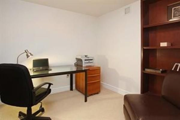A home office with a desk, a chair, and a set of shelves.