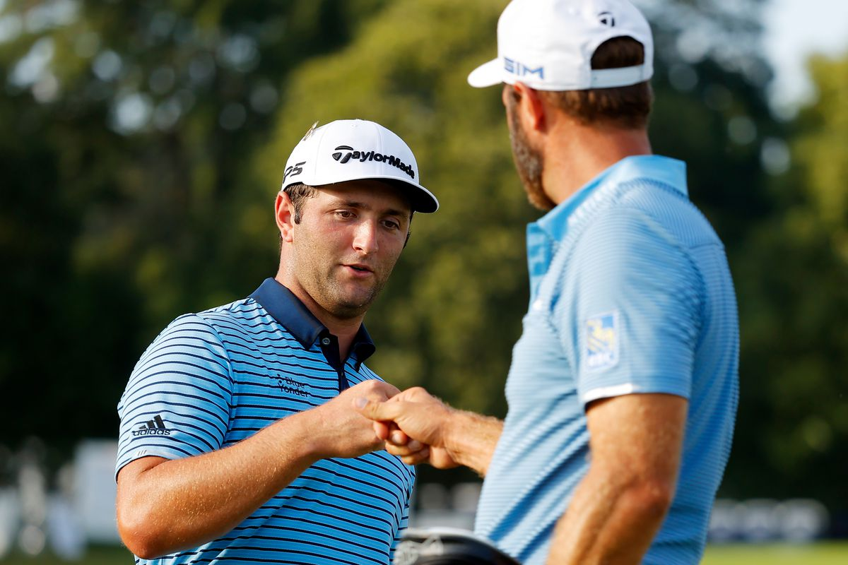 Jon Rahm of Spain and Dustin Johnson of the United States bump fists on the 18th green during the first round of the TOUR Championship at East Lake Golf Club on September 04, 2020 in Atlanta, Georgia.