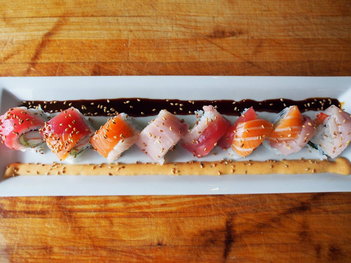 A long white plate with various sushi pieces.