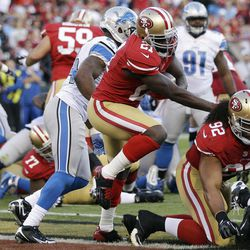 San Francisco 49ers running back Frank Gore carries the ball into the end zone for a touchdown during the second quarter of an NFL football game against the Detroit Lions in San Francisco, Sunday, Sept. 16, 2012. At right is 49ers defensive tackle Will Tukuafu (92).