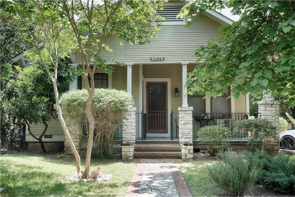 Wood frame craftsman style home with gray paint, porch, stone half-columns