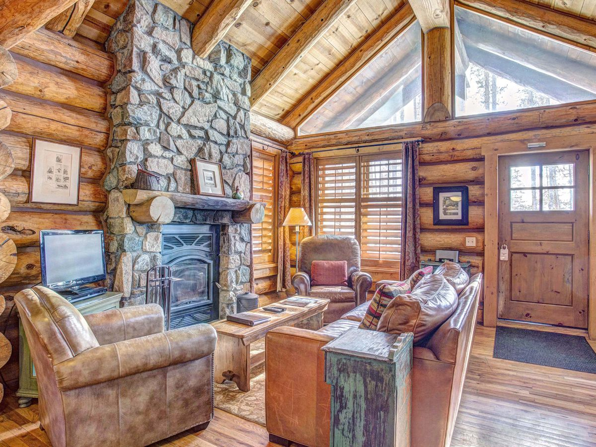 The interior of a log cabin with a couch, arm chair, and coffee table centered around a stone fireplace.