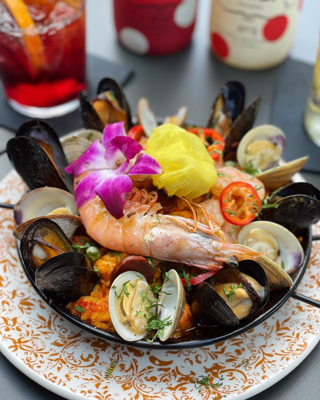 Individual sized portion of paella with whole shrimp, mussels and clams topped with cherry tomatoes and a hibiscus flower
