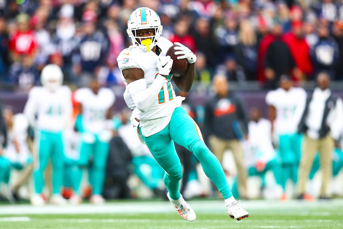 DeVante Parker of the Miami Dolphins runs the ball before being tackled by Stephon Gilmore of the New England Patriots during a game at Gillette Stadium on December 29, 2019 in Foxborough, Massachusetts.