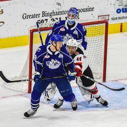 Syracuse Crunch Matt Spencer (23) gets cross checked by Binghamton Devils Brett Seney (11) in front of Crunch goalie Connor Ingram (39) in American Hockey League (AHL) action at the Floyd L. Maines Veterans Memorial Arena in Binghamton, New York on Friday, October 19, 2018. Syracuse won 4-0.
