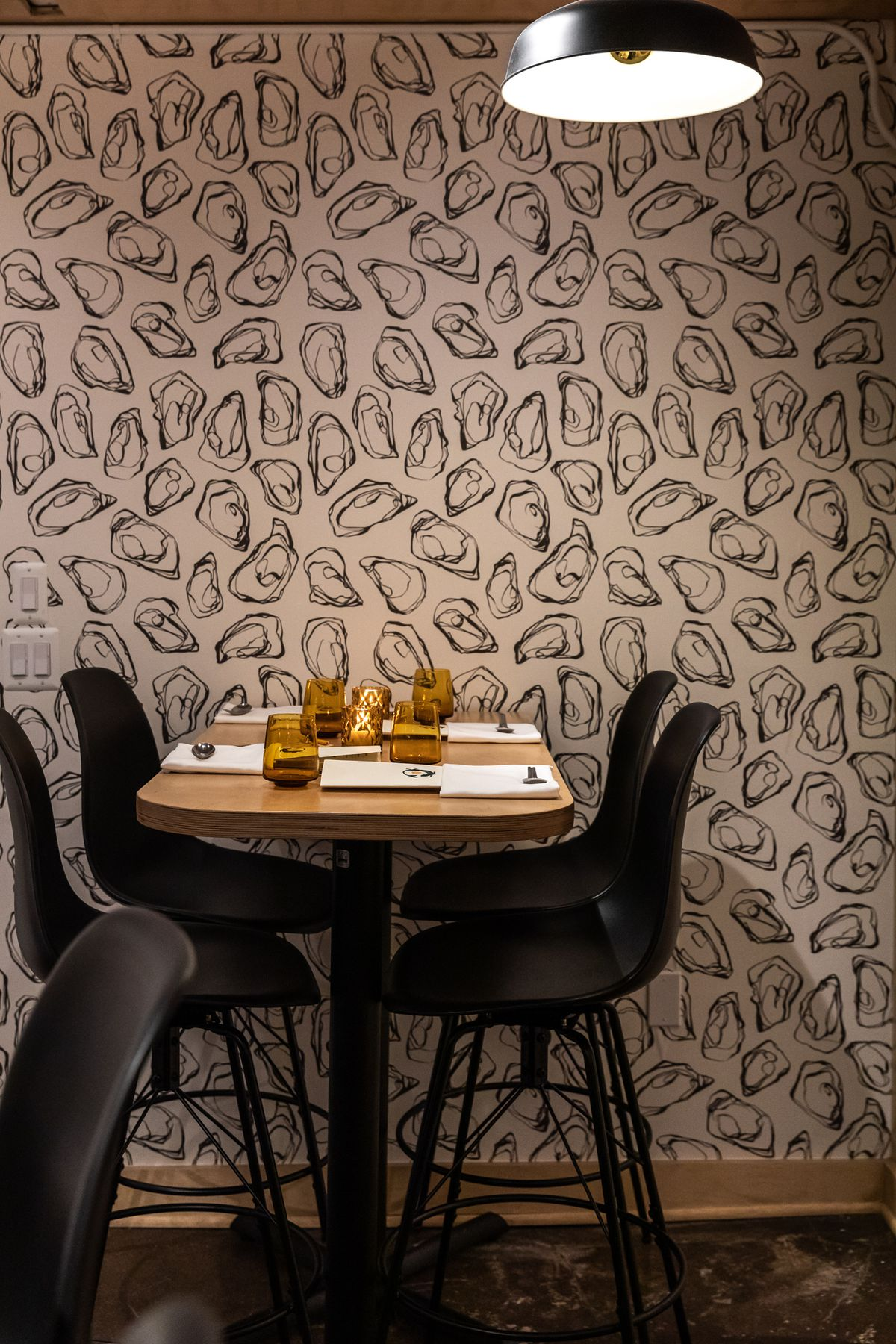 Black and white wallpaper on the back wall features illustrations of oyster shells next to a high-top table surrounded by four tall black stools.