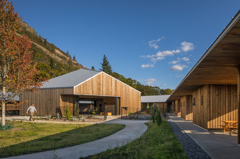 Pitch-roofed timber structure next to mountains.