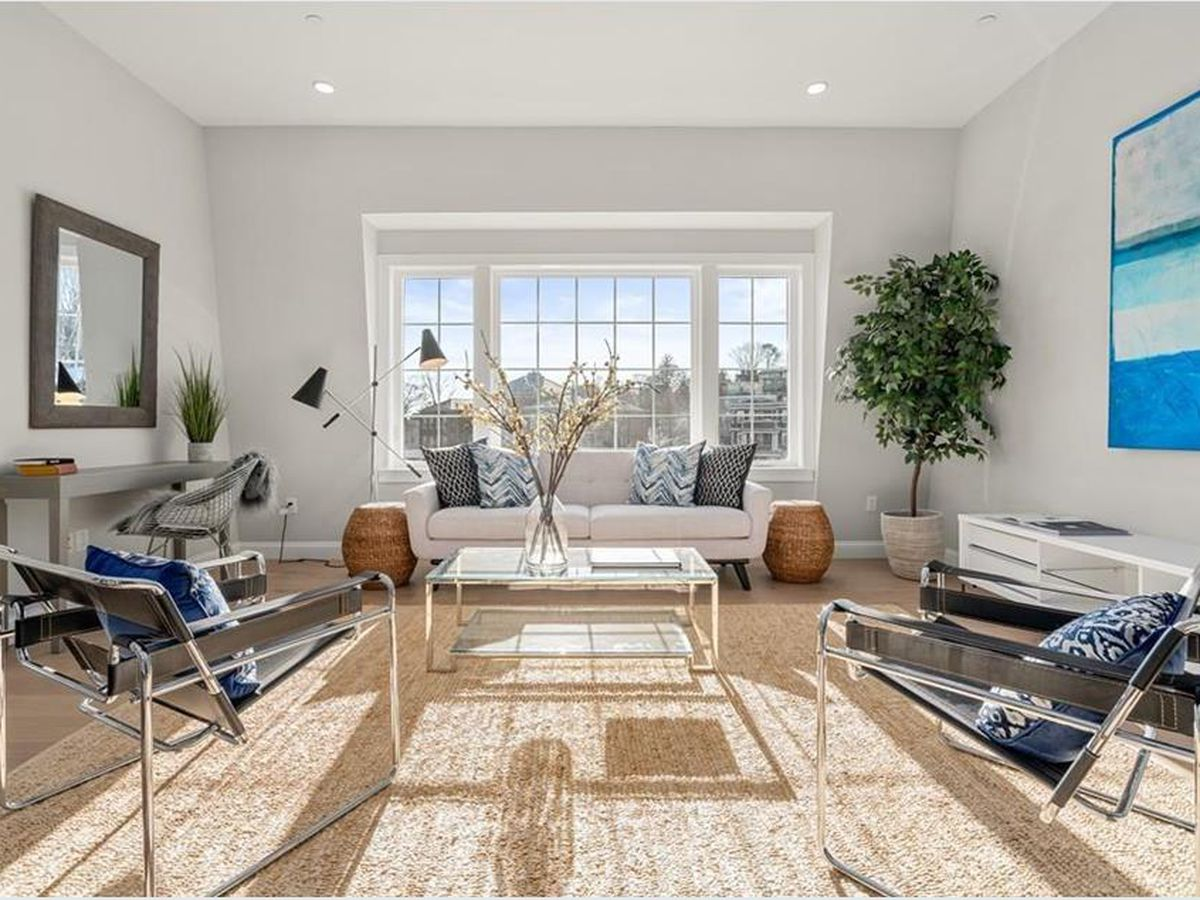 An airy living room with lots of natural light from a set of windows.