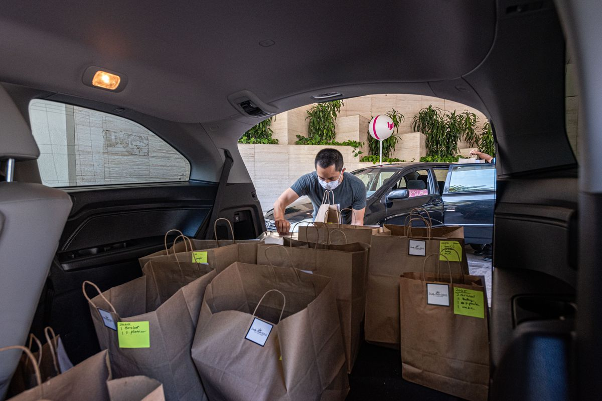 A worker loads the inside of a van with orders for delivery.