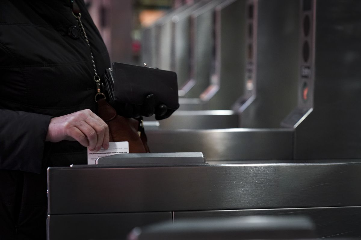 A customer swipes their Metrocard through the turnstiles.