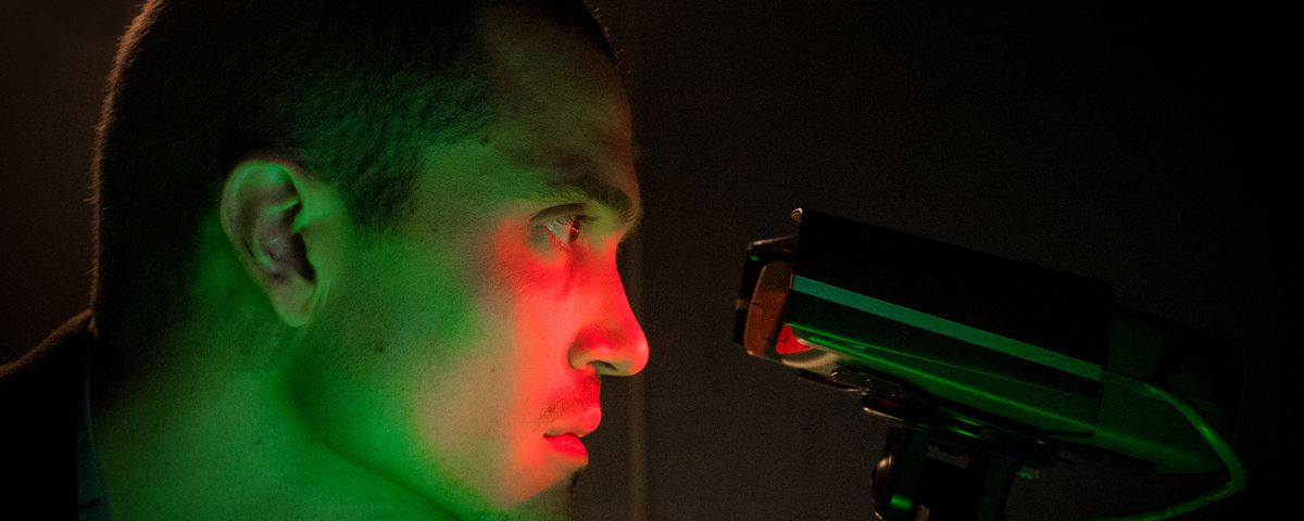 A short-haired, serious-looking Caucasian man lit in ominous dark green in an otherwise dark room stares into a device that lights up the central part of his face in vivid red.