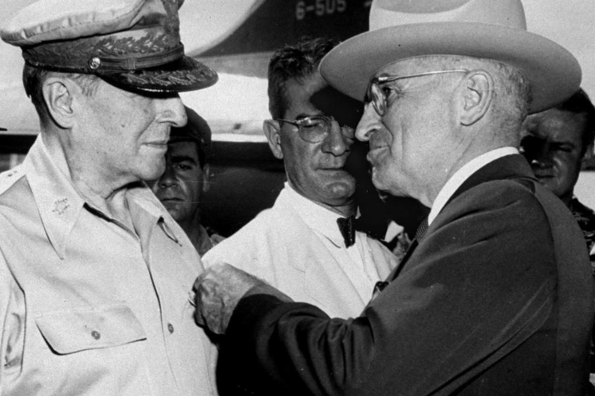 John J. Muccio, United States ambassador to Korea, who was decorated with a Medal of Merit, watches President Truman pins the Distinguished Service Medal on the shirt of Gen. Douglas MacArthur during a ceremony at the airstrip on Wake Island, in this Oct.