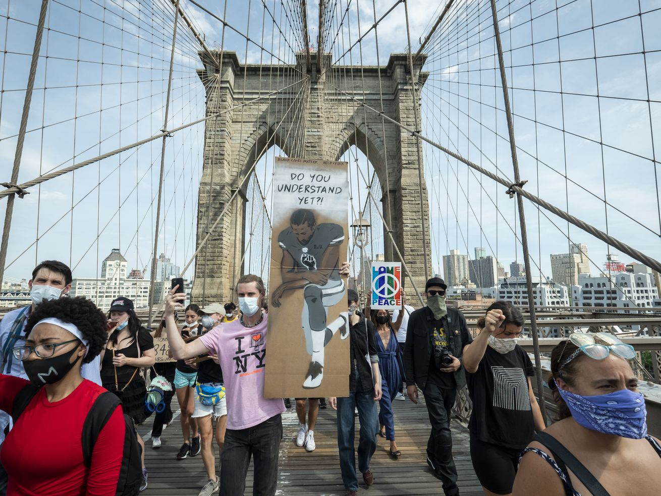 """A protester on the Brooklyn Bridge holds a sign that says, """"Do You Understand Yet?"""" with a picture of Colin Kaepernick taking a knee. June 04, 2020."""