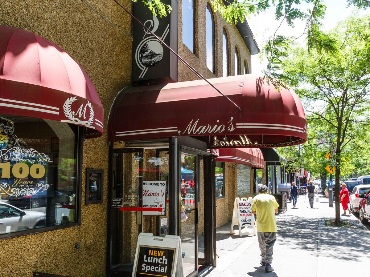 """A man in a yellow shirt walks under a red awning with the word """"Mario's"""""""