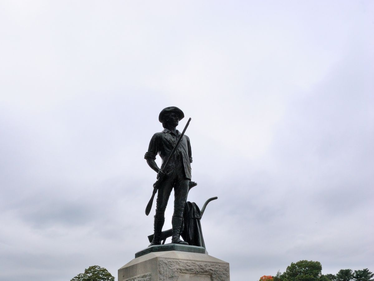 A bronze statue of a man with a riffle.