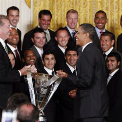 President Barack Obama carries the trophy with Real Salt Lake co-owner Dave Checketts during a ceremony in the East Room of the White House where he honored the Major League Soccer champions.