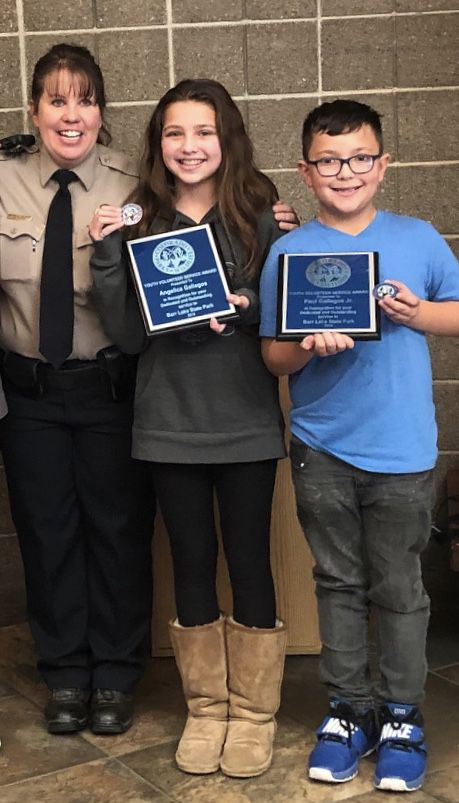 Angelica and Paul Gallegos pose with a park ranger after winning a volunteer award for their work at Barr Lake State Park.