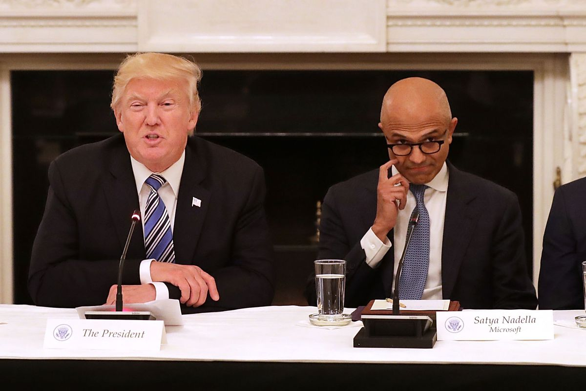 President Trump is seated between Apple CEO Tim Cook and Microsoft CEO Satya Nadella.