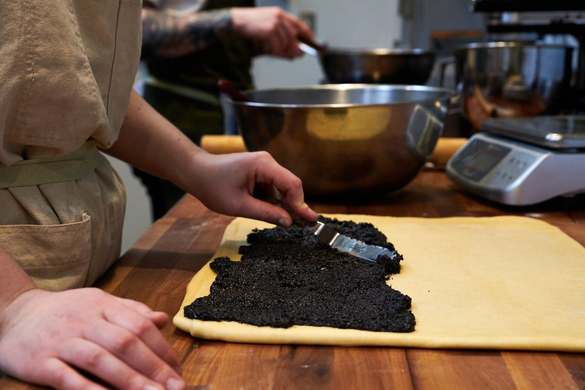 Using an icing spatula, Suda lathers a black, caviar-like substance onto a thin square of rolled and layered dough. A pastry scale and mixing bowl are just out of frame.