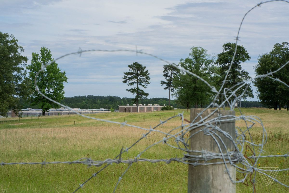 Winn Correctional Facility seen through barbed wire on a wooden fence post.