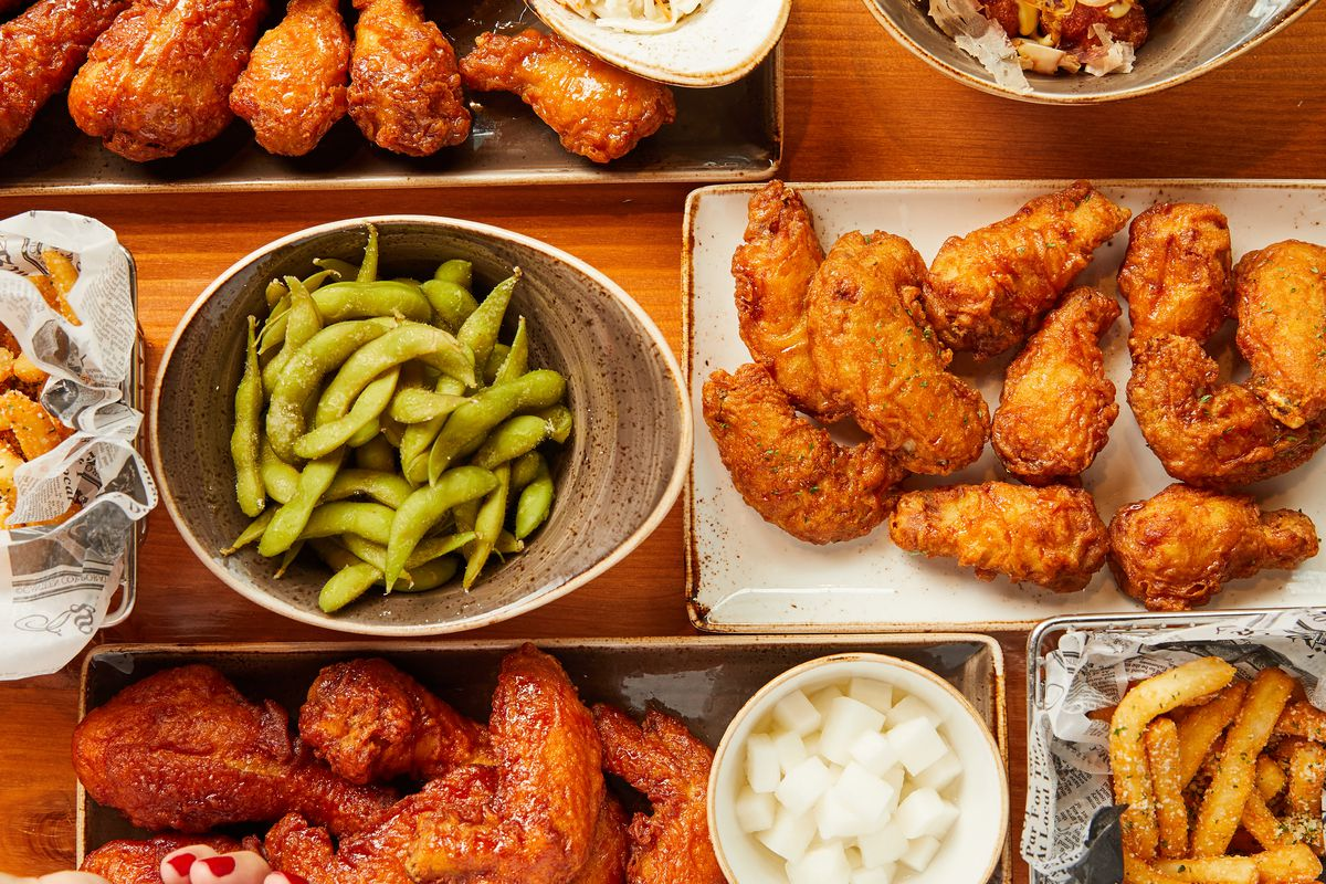 A spread of Korean fried chicken, seasoned fries, banchan, and edamame